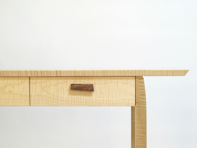 A narrow console table with drawers featuring hand shaped drawer pulls.  Solid wood furniture made by hand in the USA